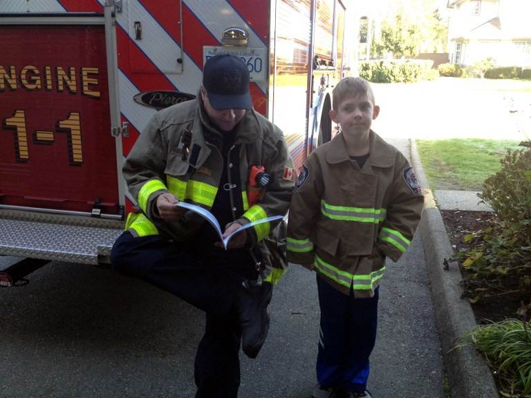 Nathan McTaggart, author of Santa and his Super Hero, with a firefighter.