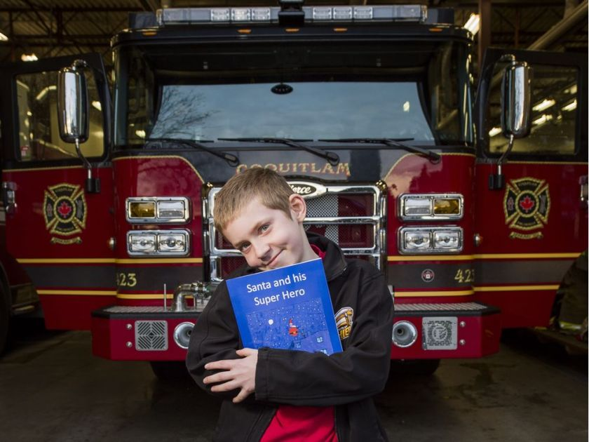 Nathan McTaggart poses in Coquitlam with the book he wrote about Santa getting stuck in the chimney and firefighters having to rescue him. RICHARD LAM / PNG